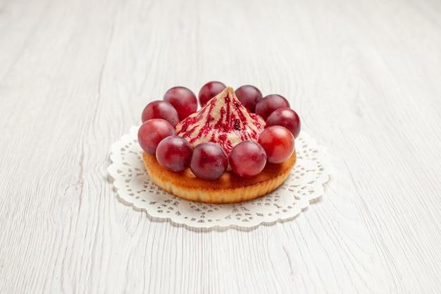Delicioso bolo de vista frontal com uvas no fundo branco