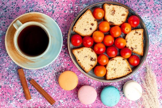 Delicioso bolo fatiado com macarons de ameixas frescas e uma xícara de chá na mesa rosa
