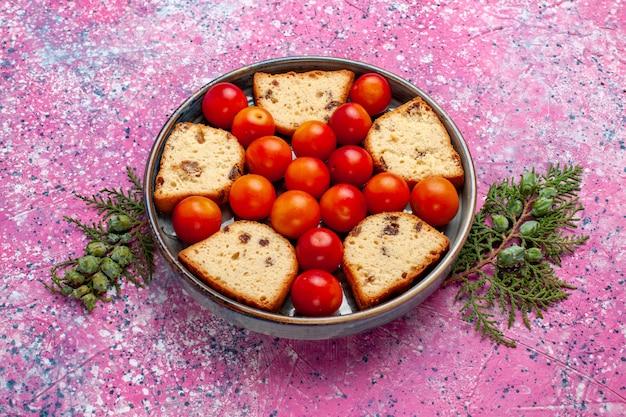 Delicioso bolo fatiado de frente com ameixas frescas azedas dentro da panela na superfície rosa