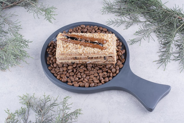 Delicioso bolo no tabuleiro escuro com grãos de café.