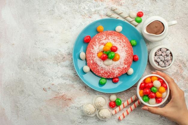 Delicioso bolo rosa com doces coloridos na superfície branca.