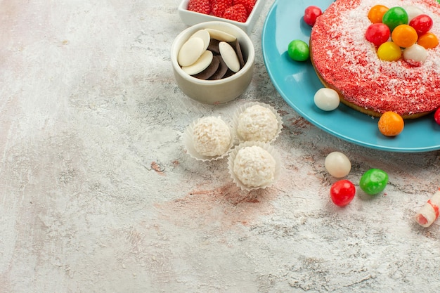 Delicioso bolo rosa com doces coloridos no fundo branco.