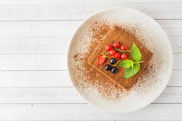 Delicioso bolo tiramisu com frutas frescas e hortelã
