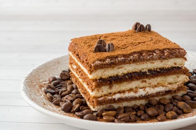 Delicioso bolo tiramisu com grãos de café em um prato em uma luz