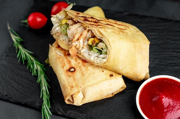 Delicioso burrito em rolos com frango, legumes e ervas em uma tábua de cortar em um fundo escuro mexicano shawarma