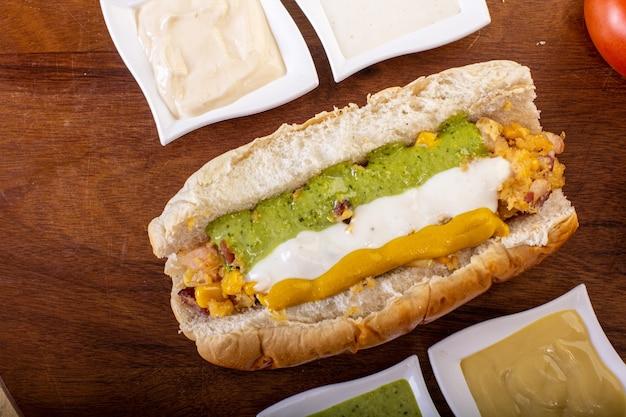 Delicioso cachorro-quente com ingredientes e em fundo colorido ou de madeira
