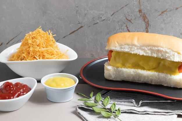 Delicioso cachorro-quente com mostarda, ketchup e palha de batata.