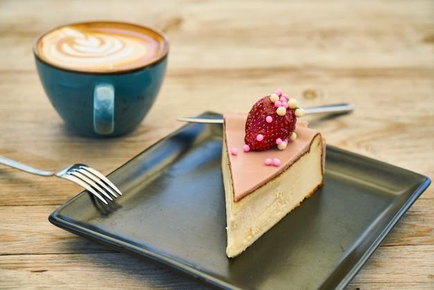 Delicioso café com leite e cheesecake na mesa de madeira