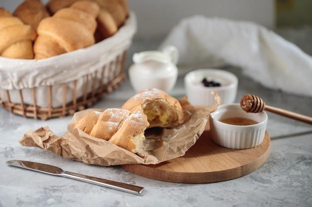 Delicioso café da manhã, close-up. um croissant quebrado com creme está sobre uma tábua de madeira, com uma tigela de mel e um jarro de creme.