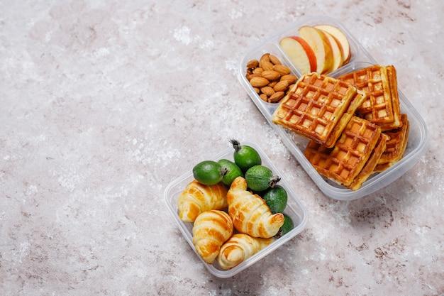 Delicioso café da manhã com amêndoas, fatias de maçãs vermelhas, waffles, croissants na lancheira plástica na luz
