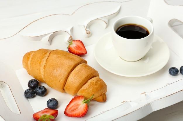 Delicioso café da manhã com café, croissant fresco e frutas vermelhas
