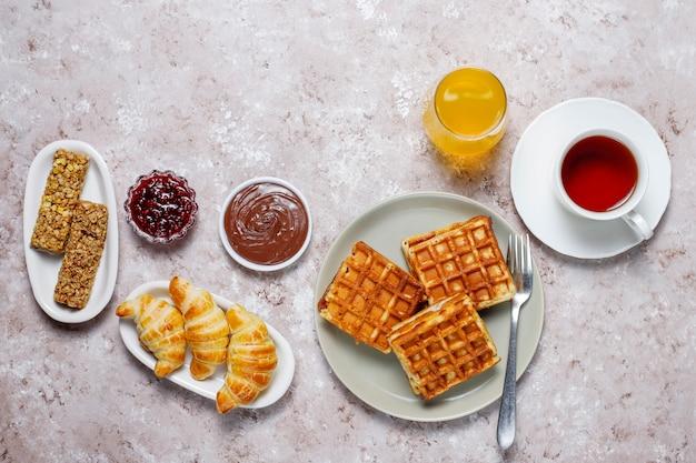 Delicioso café da manhã com café, suco de laranja, waffles, croissants, geléia, pasta de nozes na luz, vista superior
