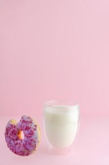 Delicioso café da manhã com copo de leite e sobremesa mordida caindo no fundo rosa pastel