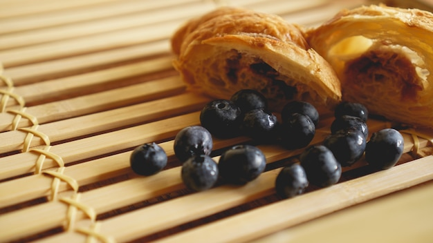 Delicioso café da manhã com croissant fresco e mirtilo na superfície de madeira