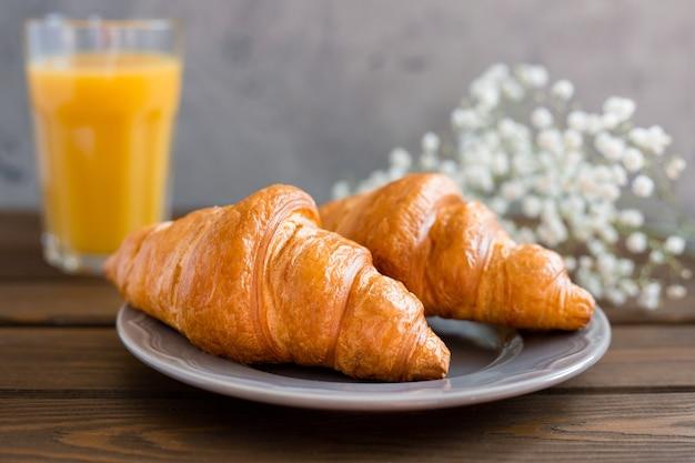 Delicioso café da manhã com croissants, flores e suco, bom dia