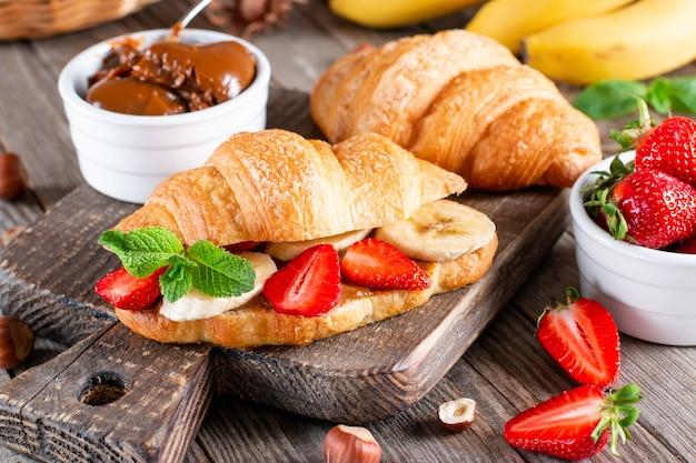 Delicioso café da manhã com croissants frescos, banana e morango na mesa de madeira