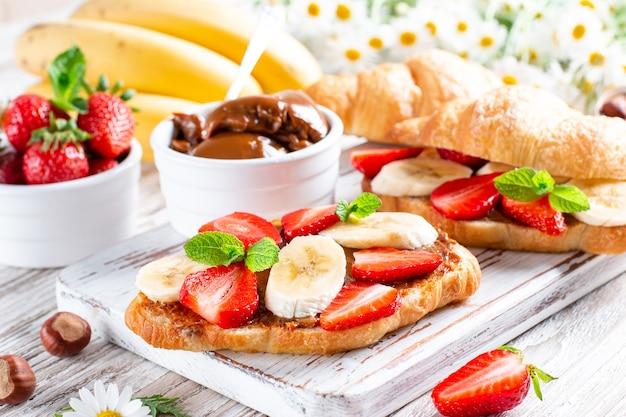 Delicioso café da manhã com croissants frescos, chocolate, banana e morango na mesa de madeira