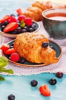 Delicioso café da manhã com croissants frescos de amêndoa, frutas e chá no fundo de madeira azul-celeste