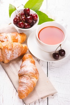 Delicioso café da manhã com croissants frescos e cerejas maduras em fundo branco de madeira
