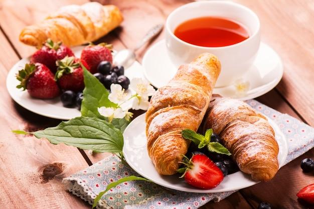 Delicioso café da manhã com croissants frescos e frutos maduros no fundo de madeira velho