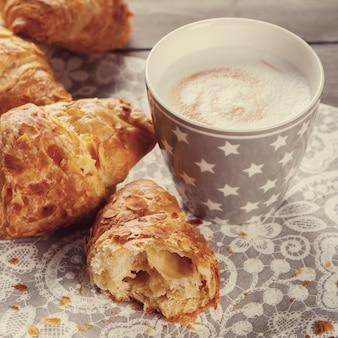 Delicioso café da manhã com croissants frescos e xícara de cappuccino no fundo cinza de madeira