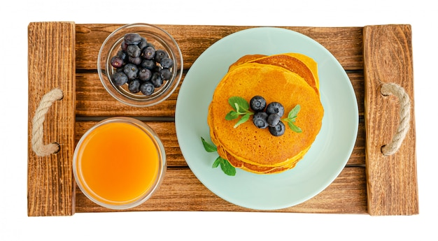Delicioso café da manhã com panquecas, mirtilos e suco de laranja na bandeja de madeira. vista isolada, superior.