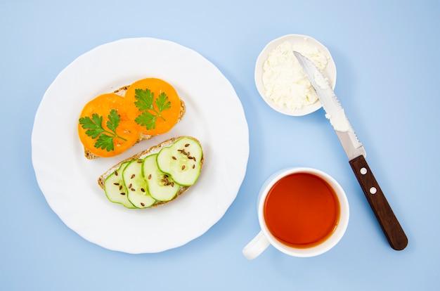 Delicioso café da manhã com sanduíches vegetarianos e uma xícara de chá