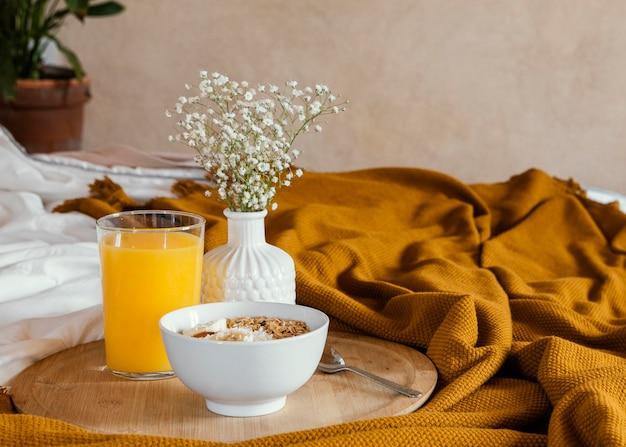 Delicioso café da manhã com tigela e suco de laranja