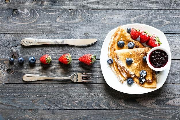 Delicioso café da manhã crepes com madeira dramática lighton