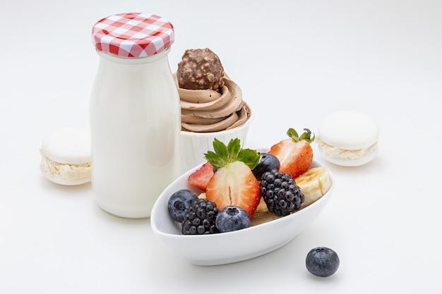 Delicioso café da manhã doce com leite, macarons, bolinho e frutas. copie o espaço. isolado.