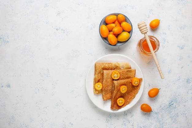 Delicioso café da manhã. feriado ortodoxo maslenitsa. crepes com cumquats e honet, vista superior