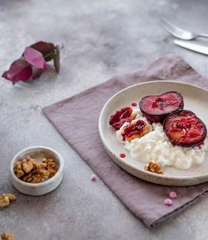 Delicioso café da manhã, iogurte com frutas e nozes em um prato de cerâmica