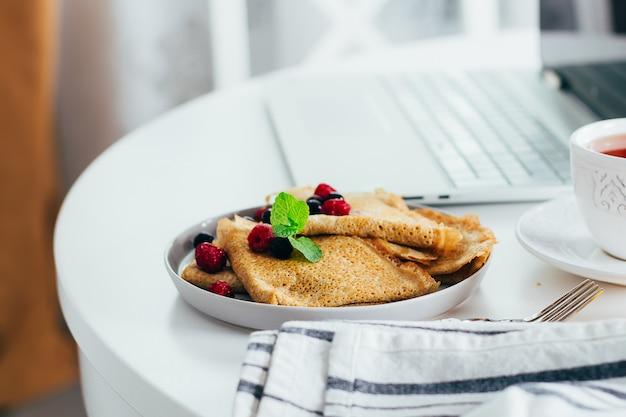 Delicioso café da manhã. mesa de trabalho branco com laptop e panquecas de crepes frescas, xícara de chá
