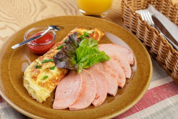 Delicioso café da manhã. omelete frito com presunto fatiado close-up