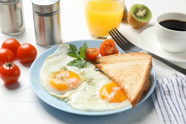 Delicioso café da manhã ou almoço com ovos fritos na mesa branca, close-up
