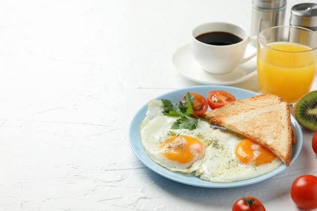Delicioso café da manhã ou almoço com ovos fritos na mesa branca, espaço para texto
