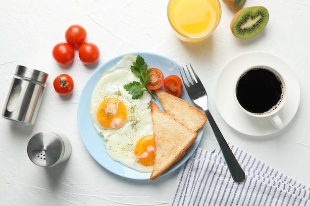 Delicioso café da manhã ou almoço com ovos fritos na mesa branca, vista superior