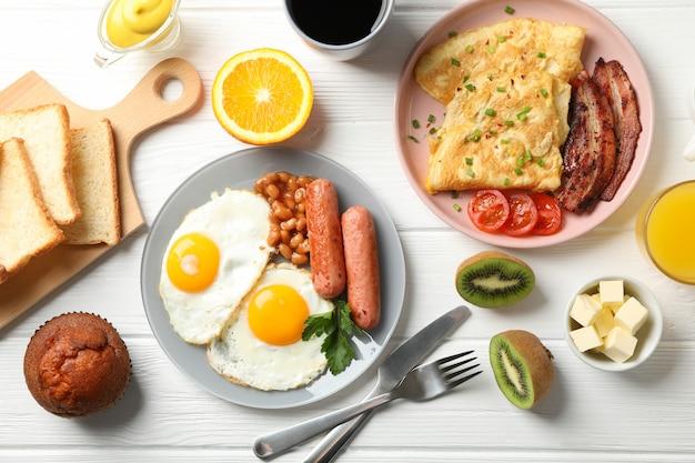 Delicioso café da manhã ou almoço com ovos fritos na mesa de madeira branca, vista superior