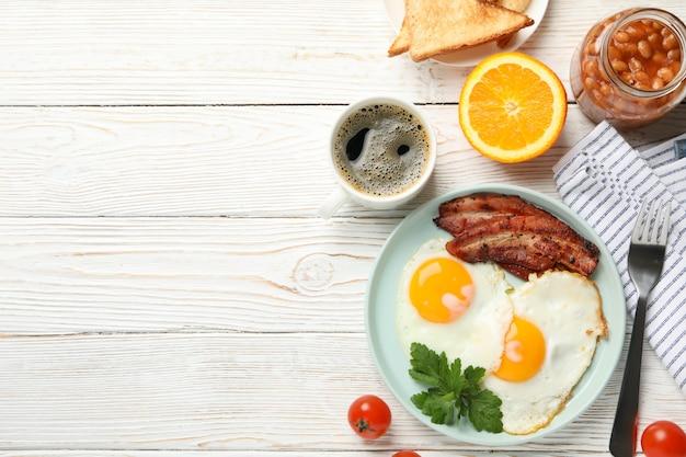 Delicioso café da manhã ou almoço com ovos fritos na superfície de madeira branca, vista superior