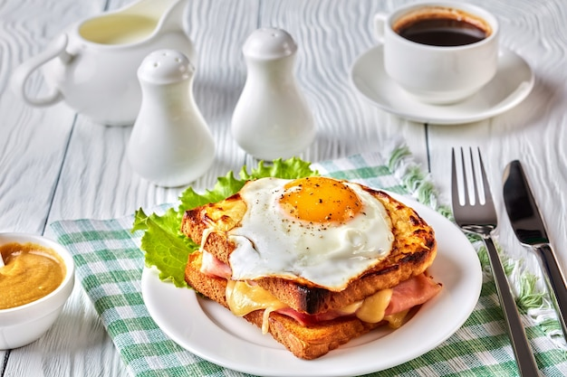 Delicioso café da manhã - torradas francesas quentes croque madame com presunto, queijo emmental derretido e ovo frito frito servido em um prato branco com uma xícara de café sobre a mesa, vista de cima, close-up