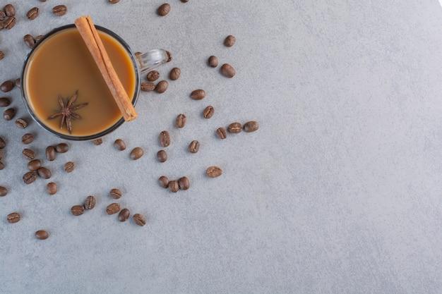 Delicioso café quente e grãos de café em fundo de pedra.