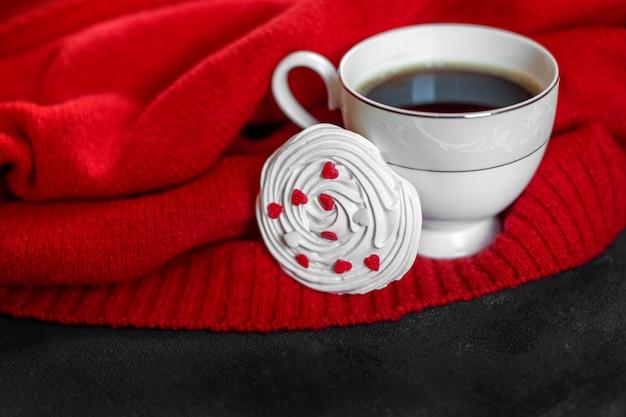 Delicioso café quente e merengue francês com corações. conceito de bebidas, lazer e estilo de vida.