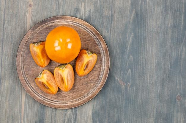 Delicioso caqui fatiado em um prato de madeira Foto gratuita