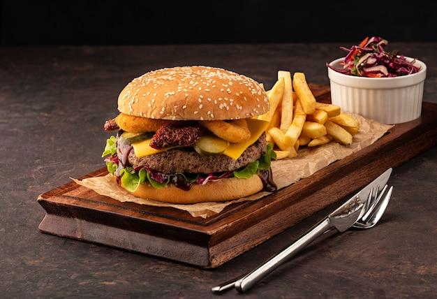Delicioso cheeseburger caseiro fresco com batatas fritas