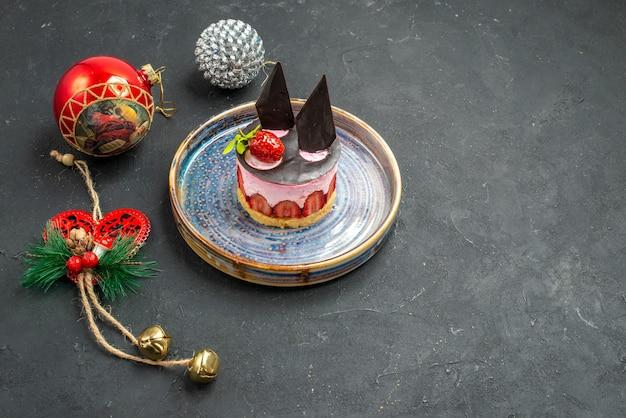 Delicioso cheesecake com morango e chocolate na placa oval de frente, brinquedos para árvore de natal no escuro com espaço livre