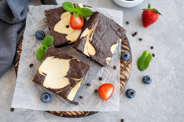 Delicioso cheesecake de brownie de chocolate com frutas frescas e hortelã em uma placa de madeira