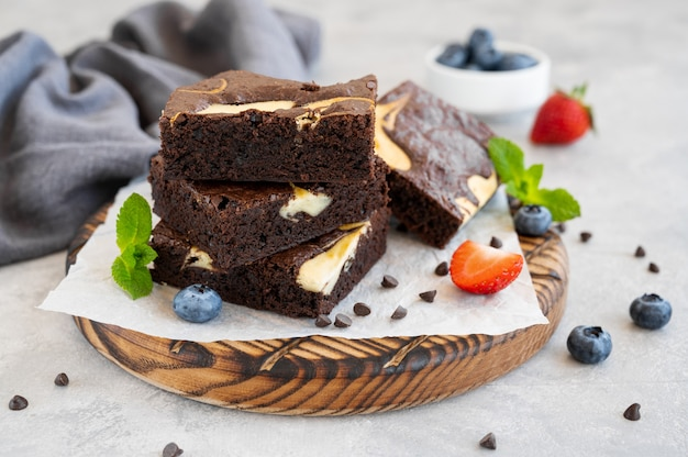 Delicioso cheesecake de brownie de chocolate com frutas frescas e hortelã