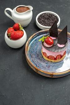 Delicioso cheesecake de frente com morango e chocolate em tigelas de prato oval com chocolate de morangos no escuro