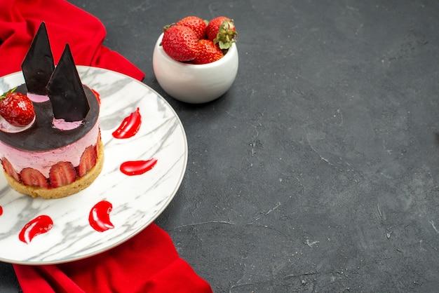 Delicioso cheesecake de frente com morango e chocolate na tigela de xale vermelho com morangos em fundo escuro isolado.