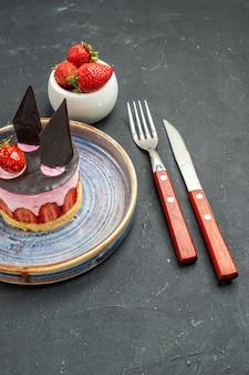 Delicioso cheesecake de frente com morango e chocolate na tigela do prato com faca de garfo de morangos no escuro